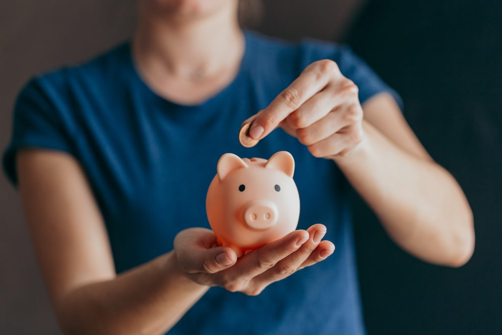 female hands hold a pink piggy bank and puts a coin there.